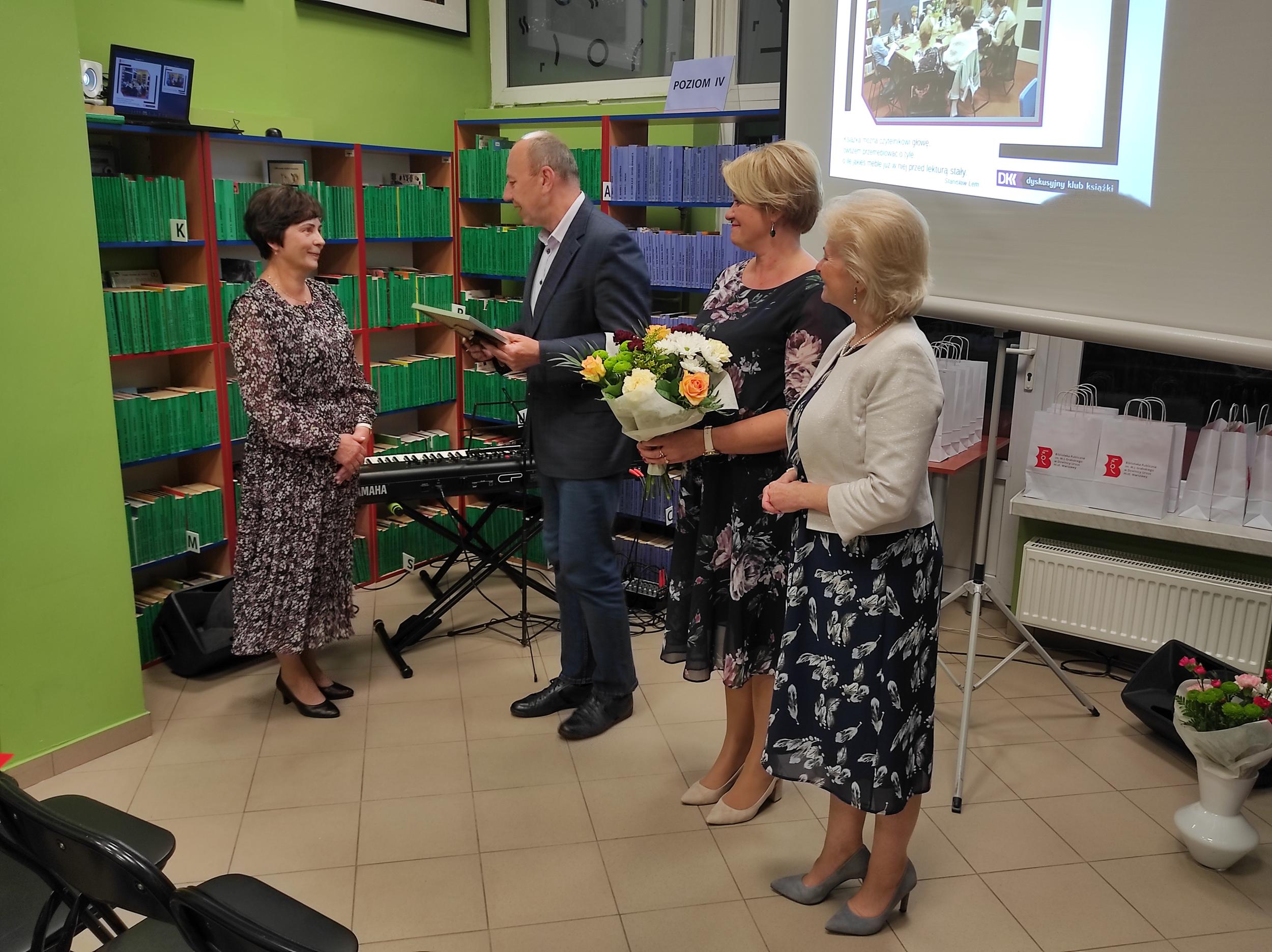 Trzy osoby stoją i gratulują kobiecie, jedna trzyma w ręku kwiaty do wręczenia jubilatce