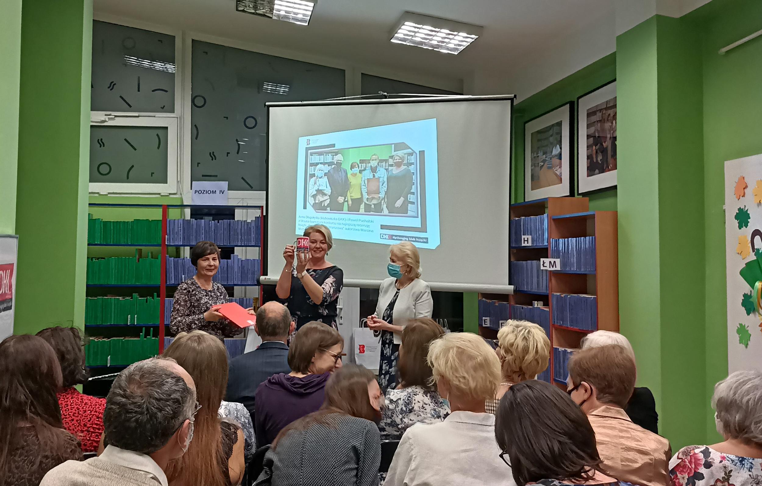 widownia i ekran z prezentacją. Przed ekranem kobieta pokazuje kubek, obok stoją dwie inne kobiety.