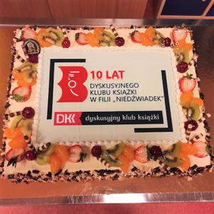 tort z napisem 10 lat i logiem biblioteki oraz dyskusyjnego klubu książki